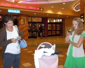 Maile and Gwen on cell phones at movie.