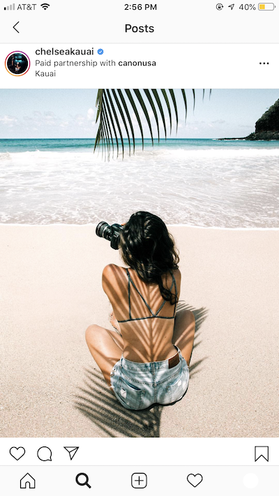 screenshot of a sponsored instagram post with a woman on a beach taking a photo under a palm tree by the ocean